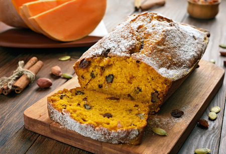 Pumpkin bread and ingredients on wooden table