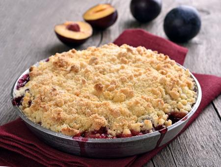 crumb: Plum crumb pie on wooden table