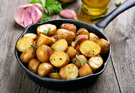 Roasted potato in frying pan on wooden background Imagens - 48489391