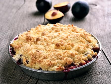 crumb: Plum crumb tart in pan on wooden background
