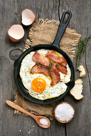 Fried eggs with bacon in frying pan on wooden background, top view