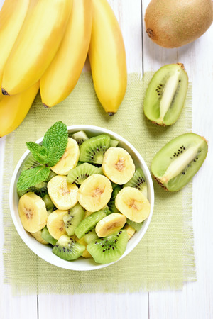 kiwi: Kiwi and banana salad in bowl and fruits on white wooden table, top view