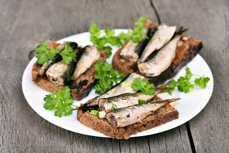 sprats: Fish sandwiches with sprats on white plate, close up view Stock Photo