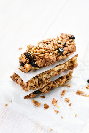 Healthy granola bars on white wooden table Stock Photo