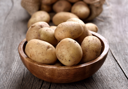 Raw potatoes in wooden bowl, close up view Stock Photo