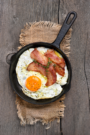 Fried eggs with bacon in frying pan, top view
