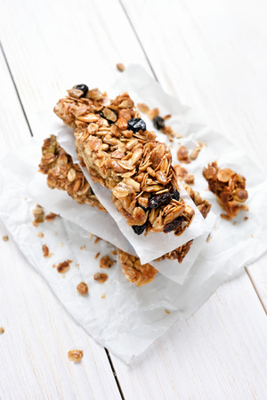 Cereal granola bars stacked on baking paper over white wooden table, top view Stock Photo
