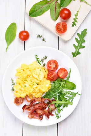 Breakfast with scrambled eggs, bacon and vegetable salad, top view