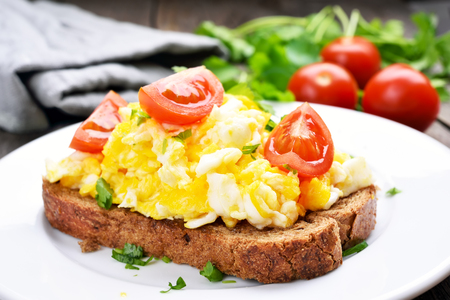 Scrambled eggs with tomato on bread, close up view