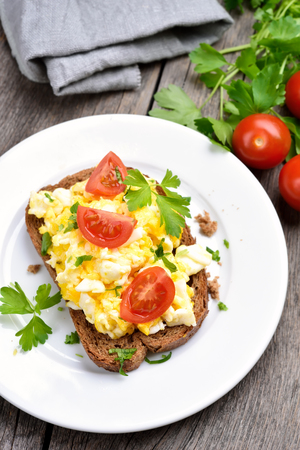 scrambled eggs: Breakfast with scrambled eggs and fresh vegetables on bread