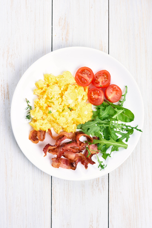 eggs and bacon: Scrambled eggs, bacon and vegetable salad on plate, top view