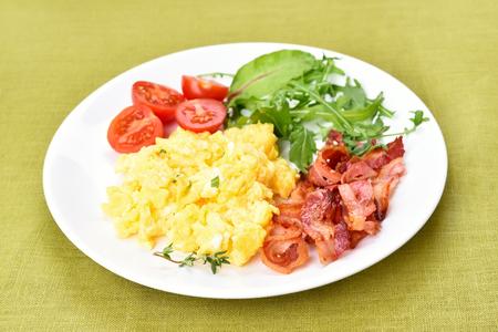 huevos revueltos: Desayuno huevos revueltos, tocino y el vehículo en la placa blanca