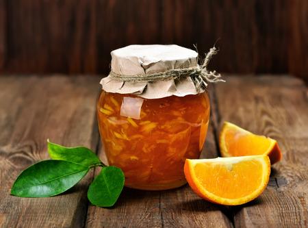 mermelada: C�tricos de naranja y mermelada de frutas rebanadas en el fondo de madera