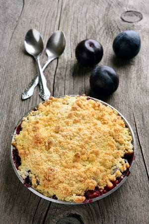 Crumble pie with plums on wooden background
