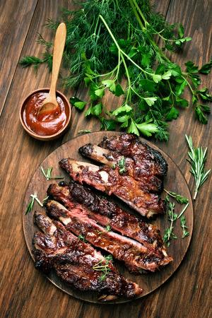 Gegrilde gesneden barbecue varkensvlees ribben op houten achtergrond, bovenaanzicht
