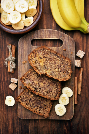 Sliced banana bread on wooden cutting board, top view Stock Photo