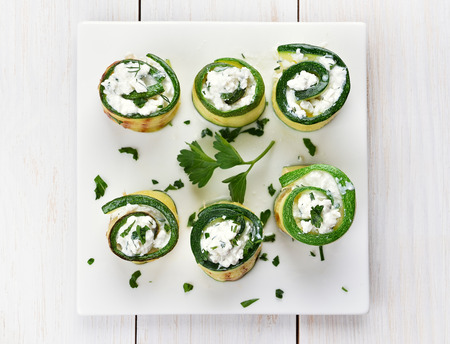 Appetizer zucchini stuffed with curd cheese and green herbs, top view Stock Photo