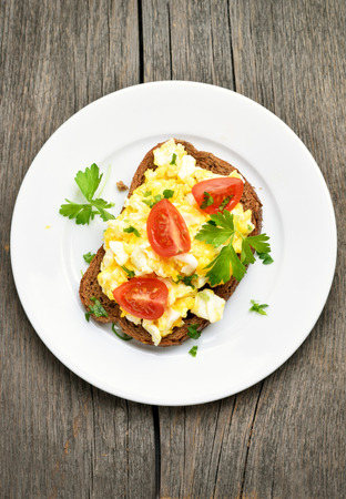Sandwich with scrambled eggs and tomatoes, top view