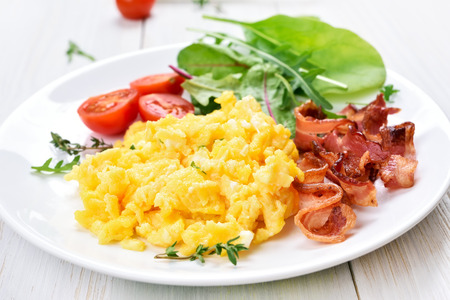 scrambled eggs: Scrambled eggs, bacon and vegetable salad on white plate