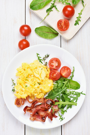Breakfast with scrambled eggs, bacon and vegetable salad on white wooden background, top view Stock Photo