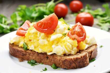 scrambled eggs: Breakfast scrambled eggs and tomato slices on bread