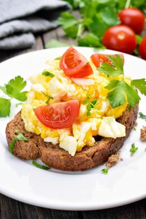 huevos revueltos: Huevos revueltos y rebanadas de tomate en el pan