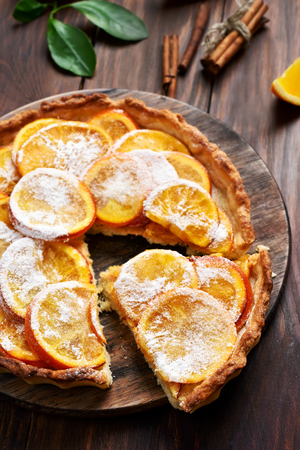 Orange pie with caramelized slices on wooden table