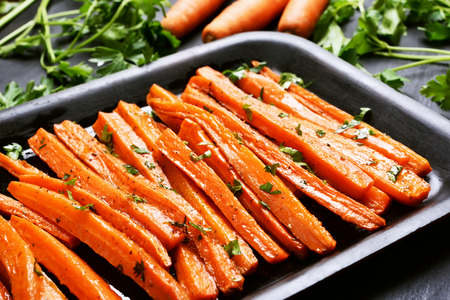 Fried carrots with green herbs in baking tray, close up Stock Photo