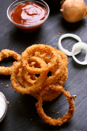 Fried onion rings on dark background