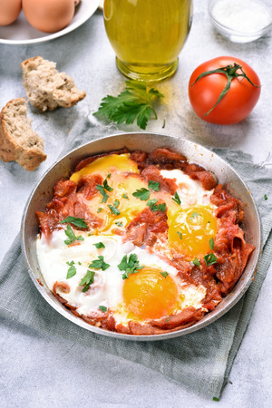 Breakfast, fried eggs with tomatoes, salami and bacon in pan
