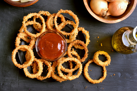 onion rings: Homemade fried onion rings with ketchup on dark background, top view Stock Photo