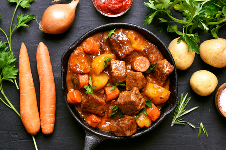 Goulash, beef stew and ingredients on dark background, top view