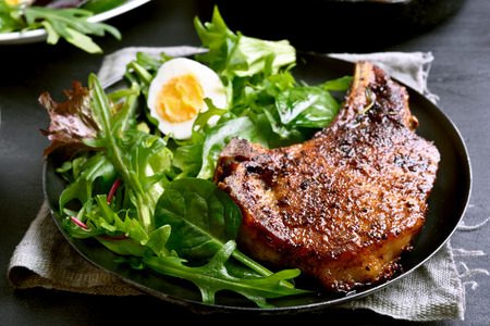 Grilled pork steak with green salad, close up view