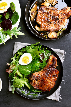 Pork chop with green salad in plate on dark background, top view Stock Photo