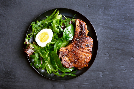 Grilled pork steak with green salad on dark background, top view