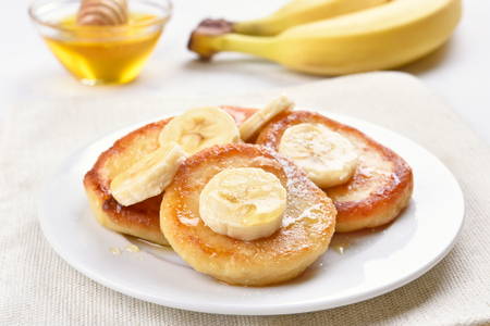 Pancakes with cottage cheese and banana slices, healthy breakfast, close up view