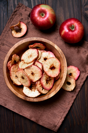 Dehydrated fruits, apples chips in wooden bowl, healthy snack. Top view