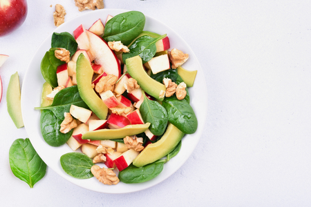 健康的な自然食品。りんご、アボカド、ほうれん草、石、明るい背景コピー スペース、上から見ると上のナッツとフルーツ サラダ。