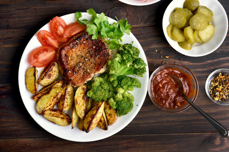Roasted meat with broccoli, potato wedges and tomato slices on wooden background, top view