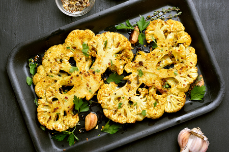 Baked cauliflower steaks with herbs and spices on baking sheet over black stone background