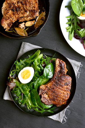 Fried pork steak with green salad, top view