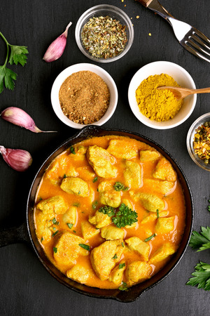 Delicious chicken curry on dark stone background. Top view, flat lay