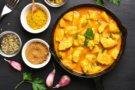 Chicken curry in frying pan on dark stone background. Top view, flat lay