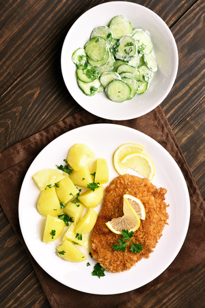 Viennese schnitzel with boiled potato and cucumber salad on wooden background. Top view, flat lay