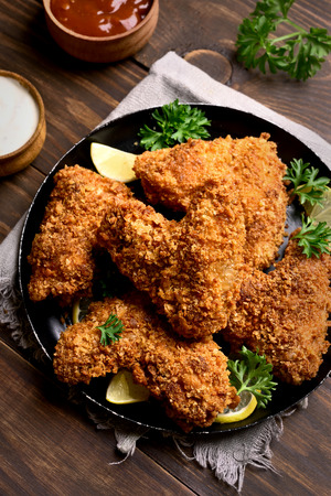 Crispy chicken wings. Dish for dinner on black plate Stock Photo
