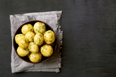 Cooked potatoes with dill in bowl on black stone background with copy space. Top view, flat lay.