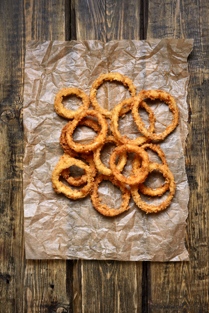 Crispy onion rings on paper over wooden background. Top view, flat lay Foto de archivo