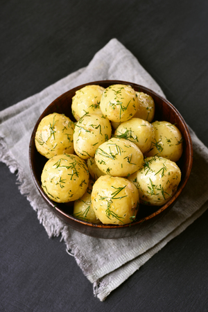 Cooked boiled potatoes with dill in bowl on dark background 版權商用圖片