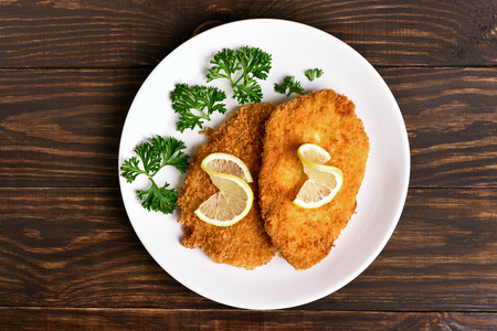 Chicken schnitzel on plate over wooden background. Top view, flat lay