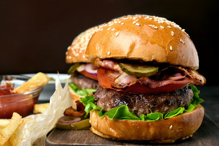 Homemade hamburger with beef, fried bacon, onion, tomato, lettuce and marinated cucumber on wooden board. Close up view